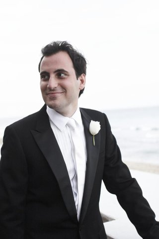groom-in-front-of-beach-with-white-boutonniere