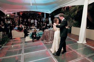 bride-and-groom-dance-on-dance-floor-in-front-of-guests