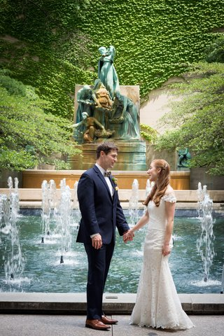 wedding-portrait-bride-and-groom-holding-hand-by-fountain-romona-keveza-wedding-dress-brown-shoes