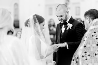 black-and-white-photo-of-bride-and-groom-exchanging-rings-during-ceremony