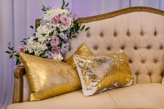 wedding-reception-lounge-tufted-settee-purple-white-flowers-greenery-gold-pillows