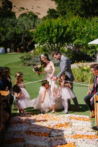 bride-and-groom-help-flower-girls-into-aisle-blocked-with-ribbon