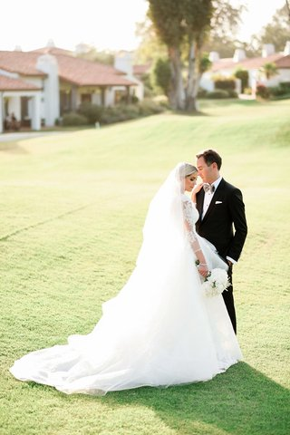 bride-in-carolina-herrera-ball-gown-in-veil-with-groom-in-custom-dolce-gabbana-tux-on-lawn