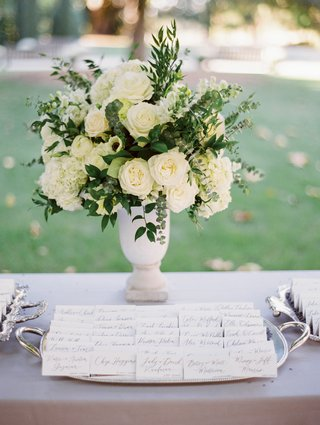escort-cards-displayed-on-silver-tray-in-front-of-ivory-roses-with-greenery-in-vase