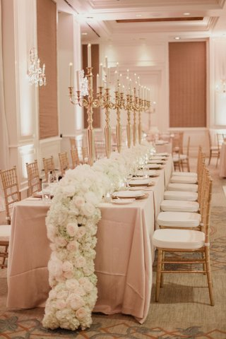 wedding-reception-long-table-with-white-flowers-cascading-on-floor-gold-candelabra-on-table