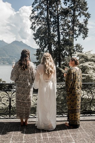 bride-in-long-white-robe-and-bridesmaids-looking-over-lake-como-with-champagne-in-hand