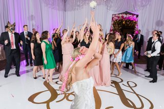 bride-looks-back-as-women-jump-for-bouquet-during-wedding-reception