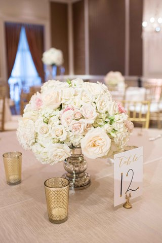 low-floral-arrangement-blush-and-white-little-bits-of-greenery-low-votives-table-number-tan-linen