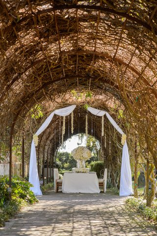 white-wedding-table-under-arch-of-vines-and-greenery