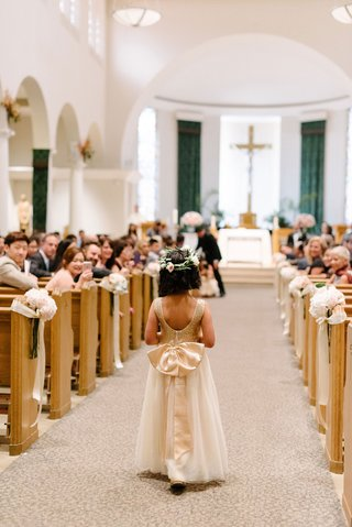 flower-girl-with-short-haircut-and-flower-crown-scoop-back-dress-with-large-bow-on-back-walking-down