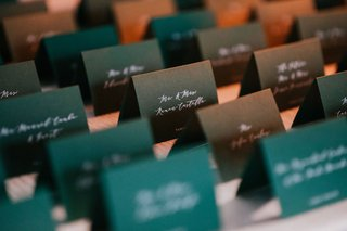 emerald-green-escort-cards-with-white-calligraphy-script-on-table-with-white-linen