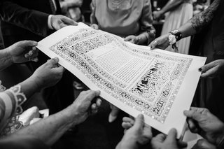 black-and-white-photo-of-ketubah-family-holding-paper-laser-cut-design-details