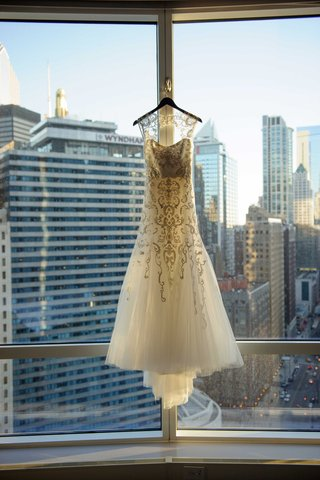 monique-lhullier-fit-and-flare-gown-with-beaded-tulle-overlay-and-keyhole-back-hanging-in-chicago