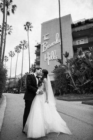 black-and-white-photo-of-bride-in-monique-lhuillier-and-groom-in-front-of-the-beverly-hills-hotel