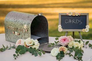 aluminum-mailbox-with-small-chalkboard-for-cards-at-wedding-roses-and-eucalyptus