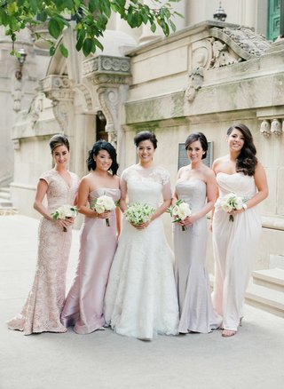 bridesmaids-in-mismatched-blush-grey-cream-dresses-holding-small-nosegays-of-garden-roses