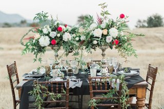 dark-reception-table-hillside-styled-shoot-black-linen-wood-chairs-vases-red-white-green-california