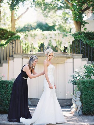 maid-of-honor-in-black-a-line-gown-zipping-up-brides-white-trumpet-gown-outdoor-ceremony-space