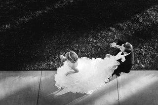black-and-white-photo-of-bride-in-demetrios-and-groom-in-ermenegildo-zegna-holds-train-champagne