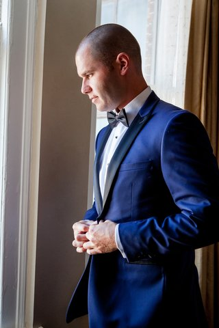 groom-buttons-navy-tuxedo-with-black-lapels-and-bow-tie