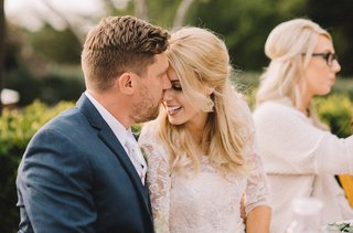 groom-kisses-brides-nose-at-wedding-reception-head-table