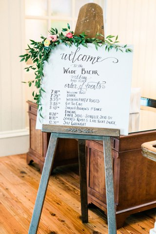 wedding-reception-easel-with-welcome-sign-and-itinerary-greenery-pink-flowers-wood