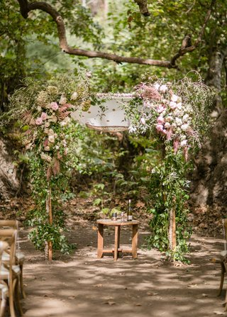 outdoor-jewish-wedding-ceremony-chuppah-made-of-tree-branches-pink-flowers-greenery-wood-table-under