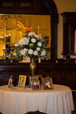 wedding-table-with-family-wedding-portraits-floral-arrangement-in-gold-stand-with-ivory-flowers