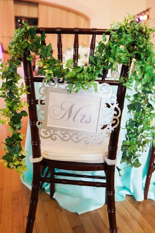wedding-reception-with-brides-seat-with-silver-mrs-sign-and-garland-of-leaves