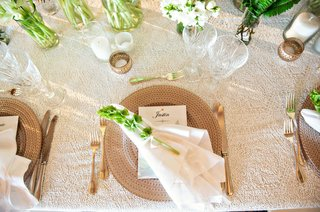 wedding-reception-texture-linens-with-charger-plate-white-napkin-green-foliage-on-place-setting-gold