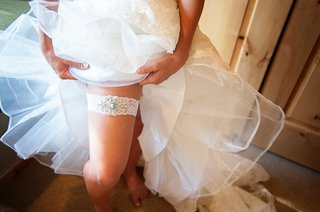 bride-pulling-up-wedding-dress-to-show-white-leg-garter-with-jewels-and-blue-stone