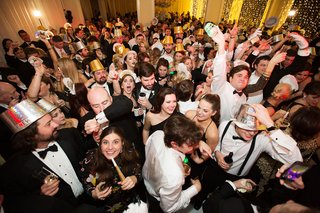 guests-on-dance-floor-with-new-years-eve-party-hats-noisemakers-and-horns-wedding-ideas-holiday