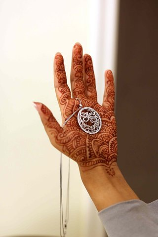 bride-with-henna-on-hand-holding-diamond-pendant