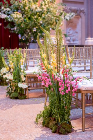 wedding-ceremony-gold-chairs-flowers-pink-yellow-greenery-growing-from-ground