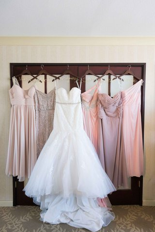 bride-bridesmaids-dresses-hanging-up-different-pink-trumpet-gown-personalized-hangers