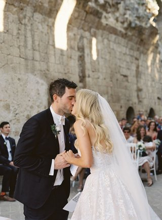 bride-and-groom-kiss-at-symbolic-wedding-ceremony-umbria-italy-old-abbey-12th-century-venue