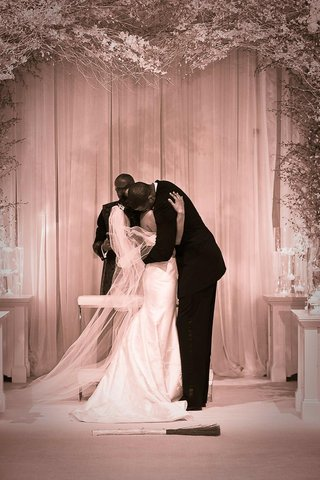 sepia-photo-of-couple-kissing-before-jumping-the-broom