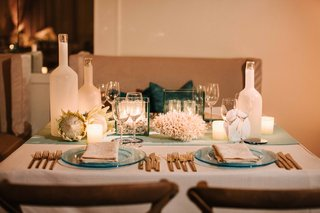 ocean-theme-wedding-with-blue-charger-coral-centerpiece-protea-candles-gold-flatware