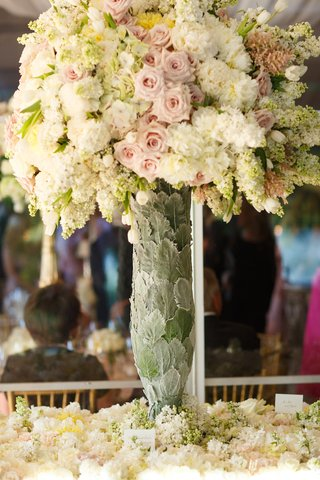 wedding-escort-card-table-covered-in-flowers-vase-covered-in-leaves-with-pink-roses-white-peonies