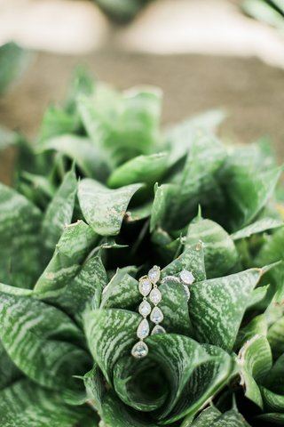 wedding-diamond-dangle-cascading-earrings-and-diamond-engagement-ring-on-greenery-foliage