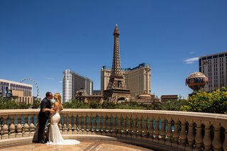 bride-and-groom-on-balcony-of-bellagio-with-view-of-the-las-vegas-strip-eiffel-tower