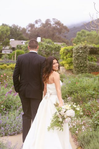 bride-turns-around-to-smile-while-walking-with-groom
