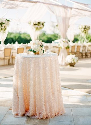 garden-wedding-reception-with-an-accent-table-with-a-sequined-pink-and-white-tablecloth-and-flowers