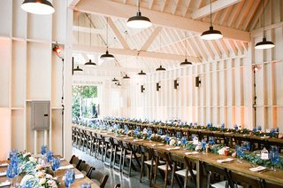 wedding-reception-at-lombardi-house-in-los-angeles-long-farm-tables-blue-glassware-greenery