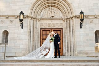wedding-portrait-bride-and-groom-kiss-in-front-of-church-doors-catholic-church-wedding