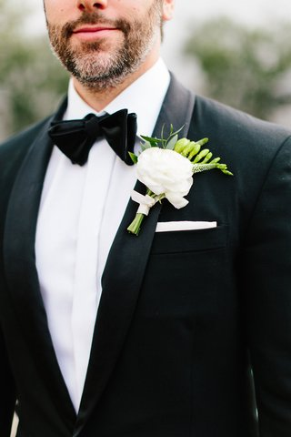 groom-boutonniere-with-white-flower-light-pink-ribbon-and-greenery-white-pocket-square-black-bow-tie