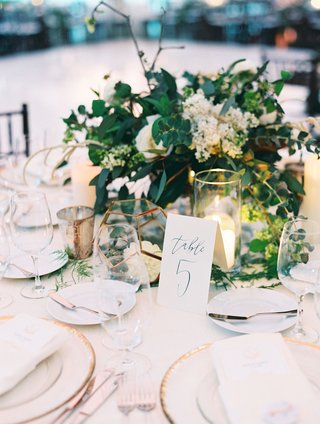 wedding-reception-centerpiece-greenery-white-flowers-calligraphy-table-number-gold-terrarium-candles