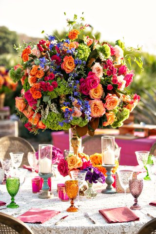 wedding-reception-lace-linen-cane-chair-green-orange-purple-goblets-orange-pink-green-flowers
