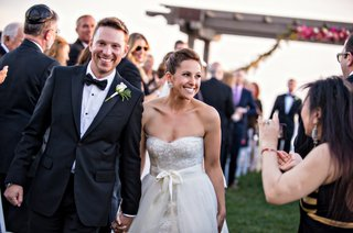 bride-in-monique-lhuillier-dress-and-groom-hold-hands-walking-up-aisle-at-outdoor-ceremony