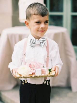 cute-ring-bearer-in-stripe-bow-tie-pink-suspenders-holding-gold-tray-with-ring-boxes-and-flowers
